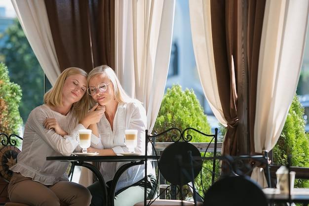 Retrato da bela mãe madura e sua filha segurando xícara sentado em casa