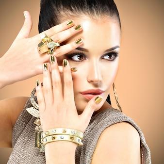 Retrato da bela moda mulher com maquiagem preta e manicure dourada