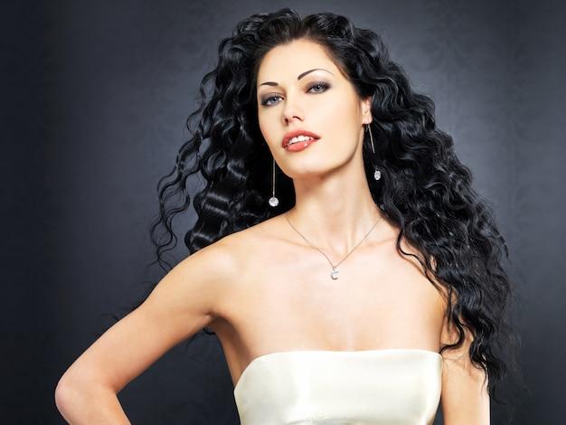 Retrato da bela moda sexy mulher com penteado longo encaracolado posa interior