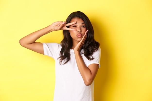 Retrato da bela modelo afro-americana mostrando o símbolo da paz e fazendo beicinho em pé glamour
