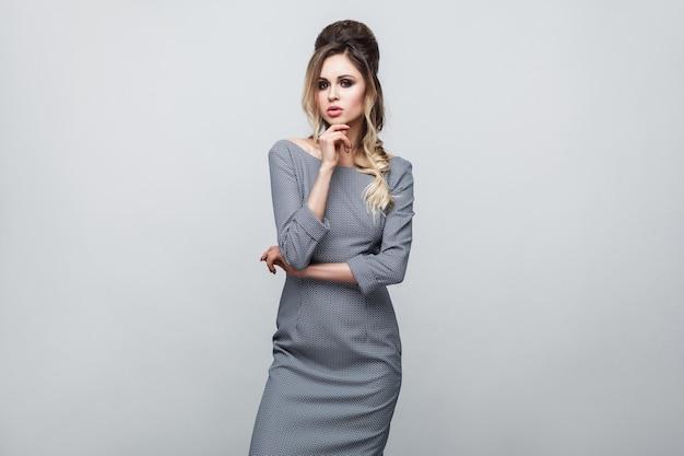 Retrato da bela modelo atraente em um vestido cinza com maquiagem e penteado em pé, posando e tocando seu queixo e olhando para a câmera. tiro de estúdio interno, isolado em fundo cinza.