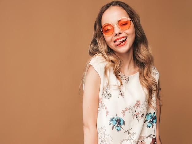 Retrato da bela modelo bonitinho sorridente com lábios rosa. garota de vestido colorido de verão e óculos de sol. levantamento modelo