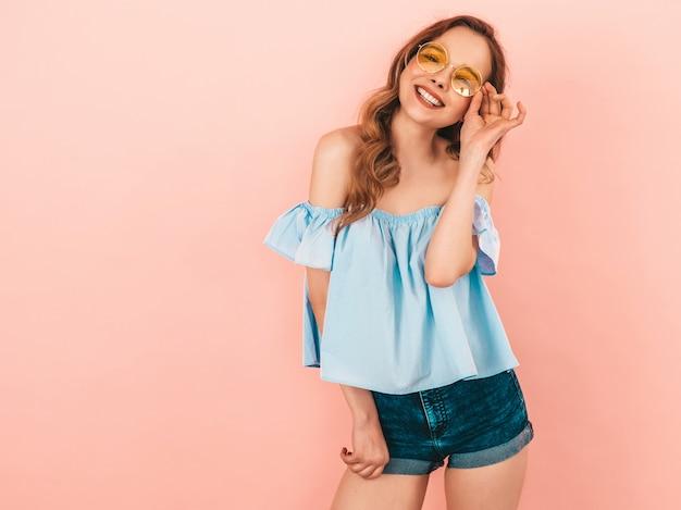 Retrato da bela modelo bonito sorridente em óculos de sol redondos. garota com roupas coloridas do verão. levantamento modelo