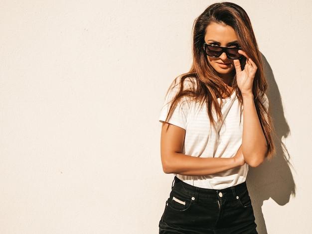 Retrato da bela modelo em óculos de sol. mulher vestida com jeans e camiseta branca de hipster de verão. mulher na moda posando perto de uma parede na rua