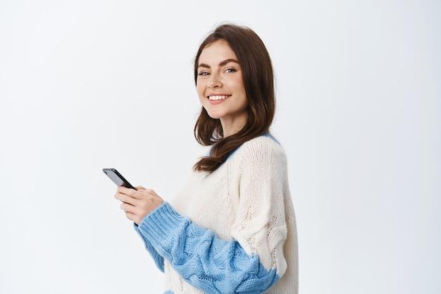 Retrato da bela modelo feminina usando o aplicativo de smartphone, em pé em seu perfil e virar o rosto com um sorriso na frente, enviando mensagem no chat de mídia social, parede branca
