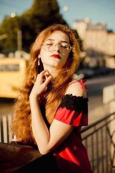 Retrato da bela modelo gengibre com os olhos fechados de óculos, posando sob a luz do sol