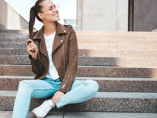 Retrato da bela modelo moreno sorridente, vestido com roupas de jeans e jaqueta hipster de verão. menina na moda, sentado nos degraus no fundo da rua. mulher engraçada e positiva em óculos de sol redondos