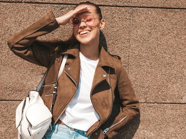 Retrato da bela modelo moreno sorridente, vestido com roupas de jeans e jaqueta hipster de verão