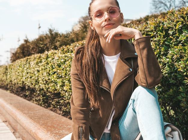 Retrato da bela modelo moreno sorridente, vestido com roupas de verão hipster jaqueta e calça jeans menina na moda, sentado no banco na rua