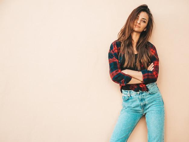 Retrato da bela modelo. mulher sexy vestida com jeans e camisa quadriculada hipster de verão. menina na moda posando perto de uma parede na rua