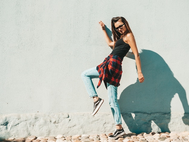 Retrato da bela modelo. mulher sexy vestida com jeans e camisa quadriculada hipster de verão. mulher na moda posando perto de uma parede na rua