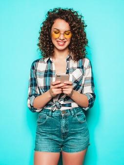 Retrato da bela modelo sorridente com penteado afro cachos, vestido com roupas de verão. garota despreocupada posando perto de parede azul. mulher usa seu telefone celular e digitando sms.