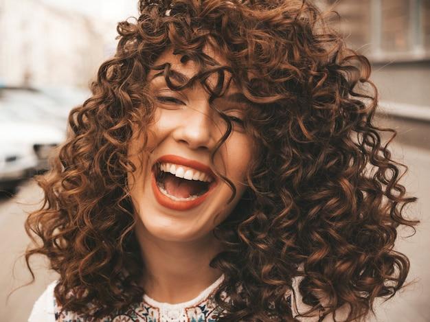 Retrato da bela modelo sorridente com penteado afro cachos.