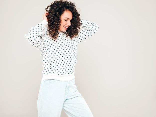 Retrato da bela modelo sorridente com penteado de cachos afro, vestido com roupas de hipster de verão. garota despreocupada sexy, posando no estúdio em fundo cinza. mulher na moda engraçada e positiva