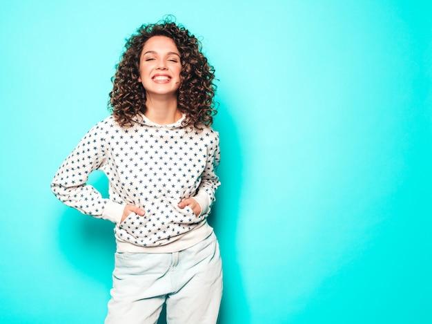 Retrato da bela modelo sorridente com penteado de cachos afro, vestido com roupas de hipster de verão. mulher na moda engraçada e positiva com capuz branco