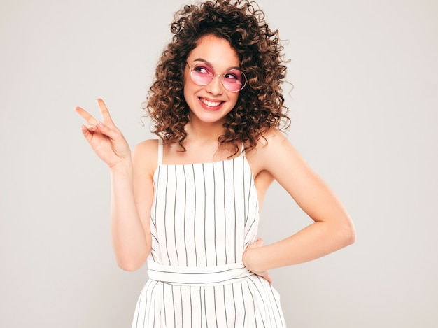 Retrato da bela modelo sorridente com penteado de cachos afro, vestido com roupas de hipster de verão. na moda, engraçada e positiva mulher mostra sinal de paz