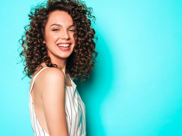 Retrato da bela modelo sorridente com penteados afro cachos, vestido com roupas de hipster de verão. garota despreocupada sexy, posando perto de parede azul. mulher na moda engraçada e positiva
