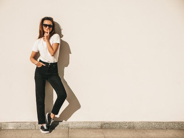 Retrato da bela modelo sorridente em óculos de sol. mulher vestida com jeans e camiseta branca hipster de verão.