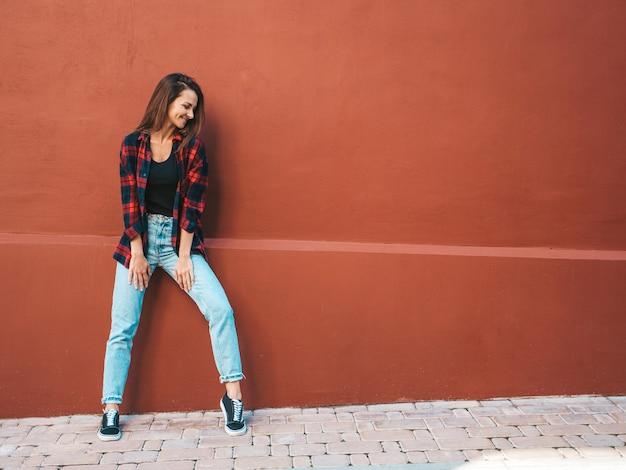 Retrato da bela modelo sorridente. mulher vestida com calça jeans e camisa quadriculada hipster de verão. menina na moda posando perto de uma parede na rua