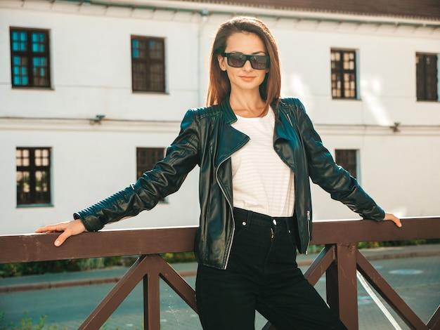 Retrato da bela modelo sorridente. mulher vestida com calça jeans e jaqueta de couro preto hipster de verão. mulher na moda posando na rua