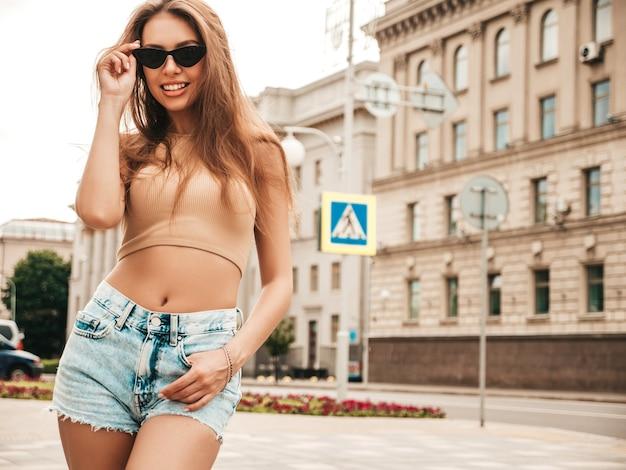 Retrato da bela modelo sorridente, vestida com shorts jeans hipster de verão