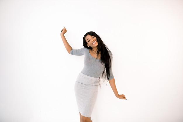 Retrato da bela mulher afro-americana positiva em pé com um braço para cima, outro braço para baixo,