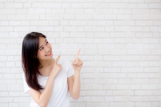 Retrato da bela mulher asiática felicidade em pé dedo apontando