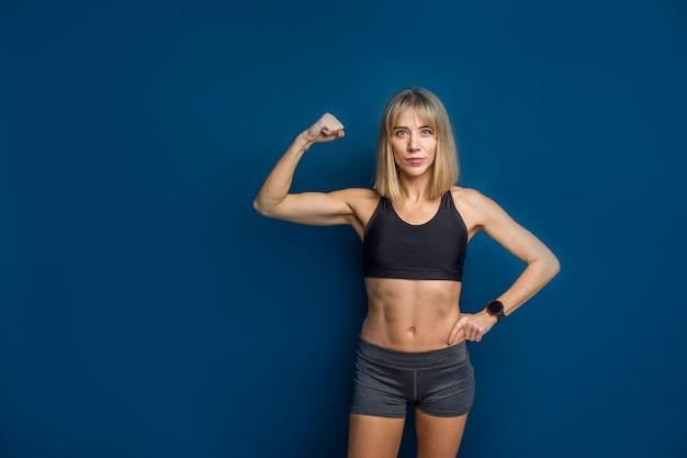 Retrato da bela mulher caucasiana atlética no sutiã esportivo e shorts mostrando o bíceps da mão dela.