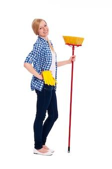 Retrato da bela mulher de limpeza com vassoura