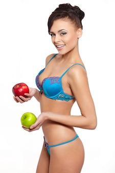 Retrato da bela mulher morena sorridente em lingerie branca com dieta de maçã verde e vermelha, isolada no branco