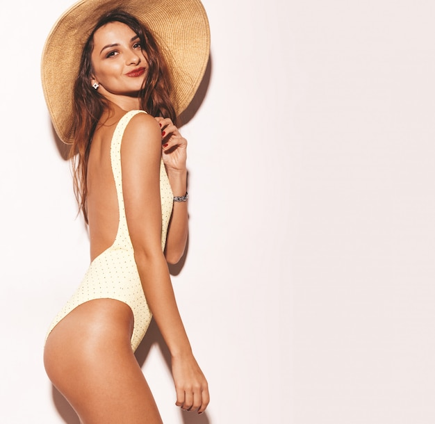 Retrato da bela mulher morena sorridente sexy. garota vestida de lingerie de corpo amarelo casual de verão e chapéu grande. modelo isolado