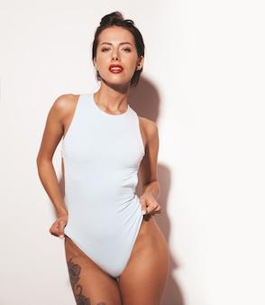 Retrato da bela mulher morena sorridente sexy. garota vestida de lingerie de corpo casual verão azul. modelo isolado no fundo branco