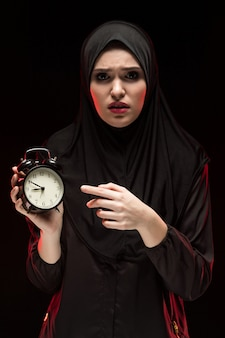 Retrato da bela mulher muçulmana assustada assustada séria usando hijab preto segurando o despertador em fundo preto