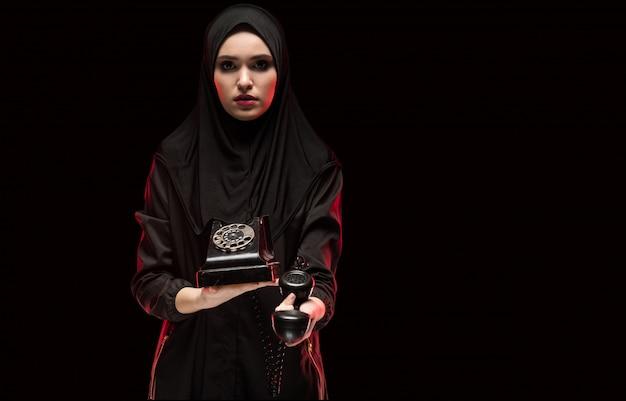 Retrato da bela mulher muçulmana assustada com medo usando o hijab preto, oferecendo telefone para ligar como conceito de escolha no fundo preto