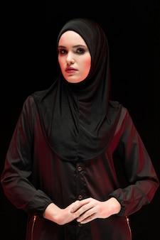 Retrato da bela mulher muçulmana jovem arrogante vestindo preto hijab como conceito conservador da moda com a mão na mão