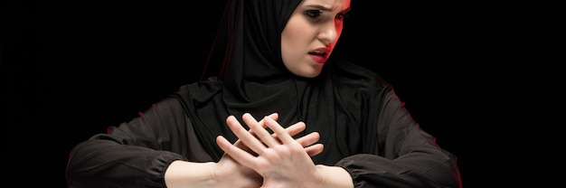 Retrato da bela mulher muçulmana jovem assustada com medo desesperada, vestindo hijab preto, mostrando o sinal de stop em fundo preto