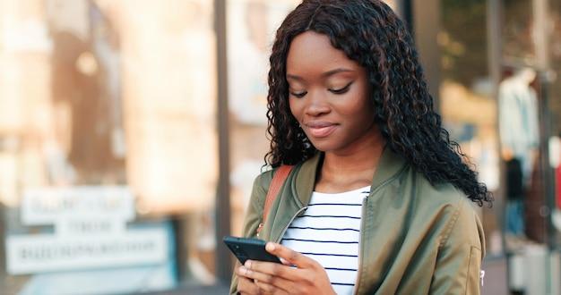 Retrato da bela mulher multirracial, mostrando um sorriso encantador e dentes saudáveis, enquanto caminhava com seu smartphone na rua. conceito de pessoas e gadgets