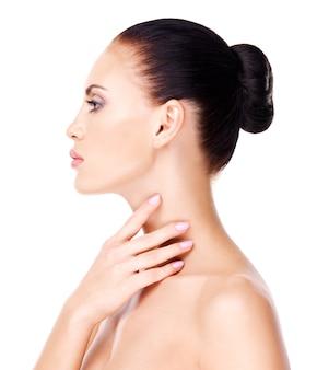 Retrato da bela mulher que toca o pescoço pelos dedos - isolado no branco