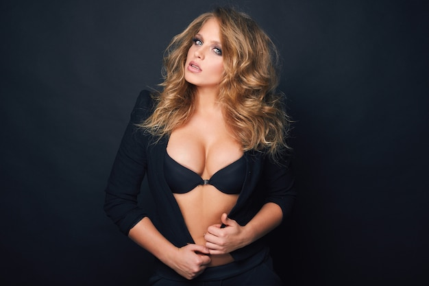 Retrato da bela mulher sexy loira em fundo preto