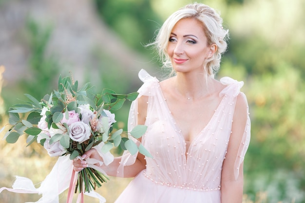 Retrato da bela noiva com buquê de flores na natureza. fotografia de belas artes.