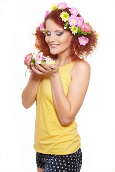 Retrato da bela ruiva sorridente mulher de gengibre no pano amarelo com flores coloridas rosa amarelas no cabelo isolado no branco segurando flores