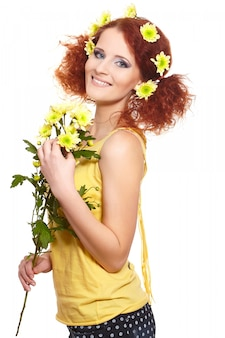 Retrato da bela ruiva sorridente mulher de gengibre no pano amarelo segurando flores amarelas e flores no cabelo isolado no branco