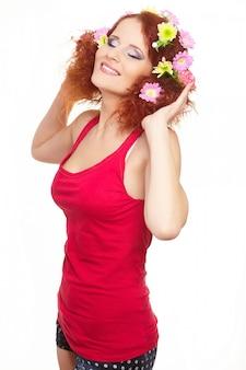 Retrato da bela ruiva sorridente mulher ruiva em pano vermelho com flores coloridas rosa amarelas no cabelo isolado no branco