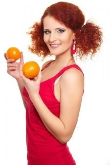 Retrato da bela ruiva sorridente mulher ruiva em pano vermelho isolado no branco com laranja