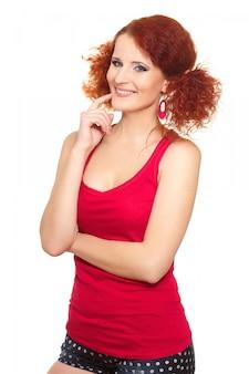 Retrato da bela ruiva sorridente mulher ruiva em pano vermelho isolado no branco