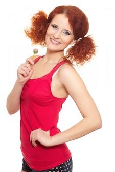 Retrato da bela ruiva sorridente mulher ruiva no pano vermelho com doce isolado no branco