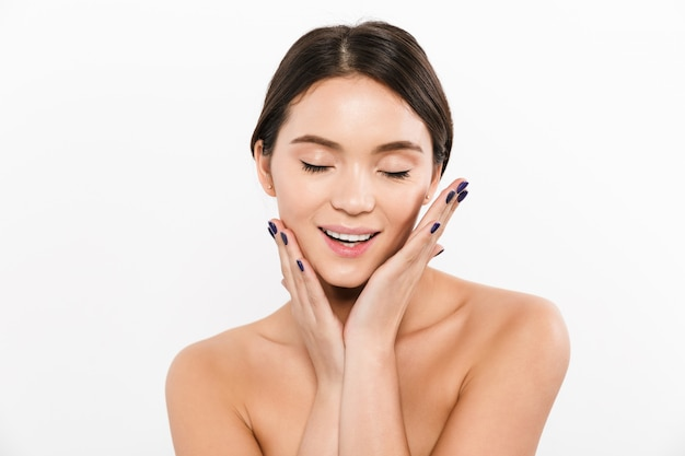 Retrato da beleza da bela mulher asiática com cabelos castanhos e esmaltes sorrindo enquanto toca seu rosto limpo e saudável, isolado sobre o branco