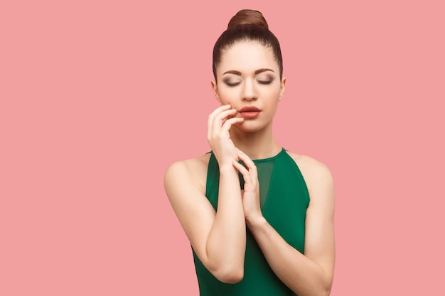 Retrato da beleza da calma séria bela jovem com coque penteado e maquiagem em pé de vestido verde, com os olhos fechados e tocando seu rosto. foto de estúdio interno, isolada em fundo rosa