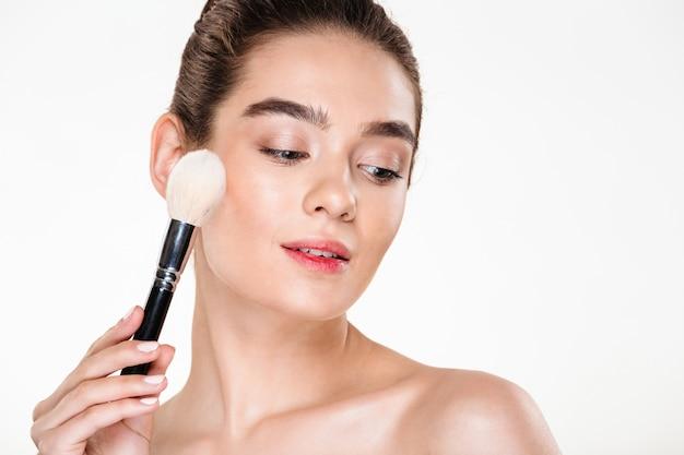 Retrato da beleza da encantadora fêmea jovem com pele fresca, aplicar maquiagem usando pincel macio com o rosto para baixo