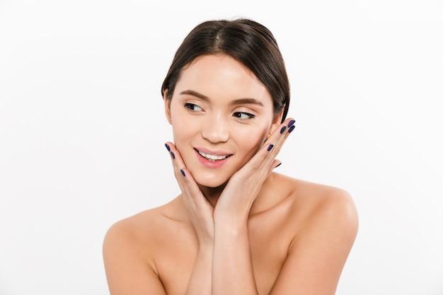 Retrato da beleza da jovem mulher asiática com cabelos castanhos e esmaltes sorrindo enquanto toca seu rosto saudável e macio, isolado sobre o branco